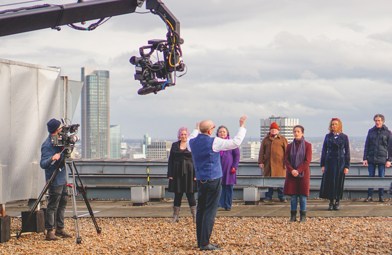 Chorus Director William Spaulding and the chorus in rehearsal for ROH Unmasked on the rooftop of the Royal Opera House ©2021 ROH. Photograph by Danielle Patrick