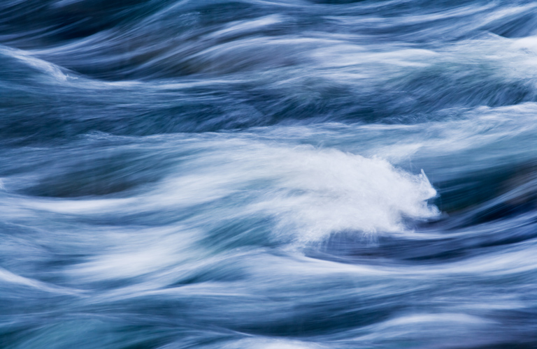 Water rushing by in a river forming an abstract pattern © Howard Grill