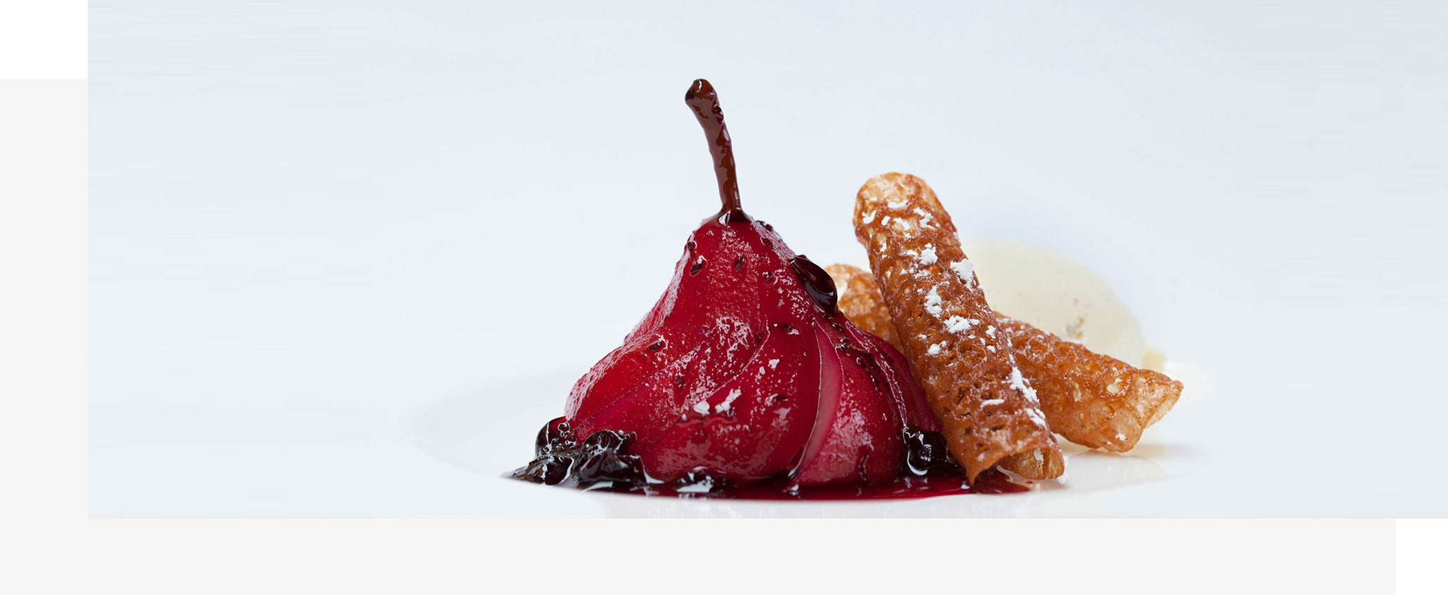 A blackcurrant poached pear served with brandy snap wafers and vanilla icecream, served in the Royal Opera House restaurants