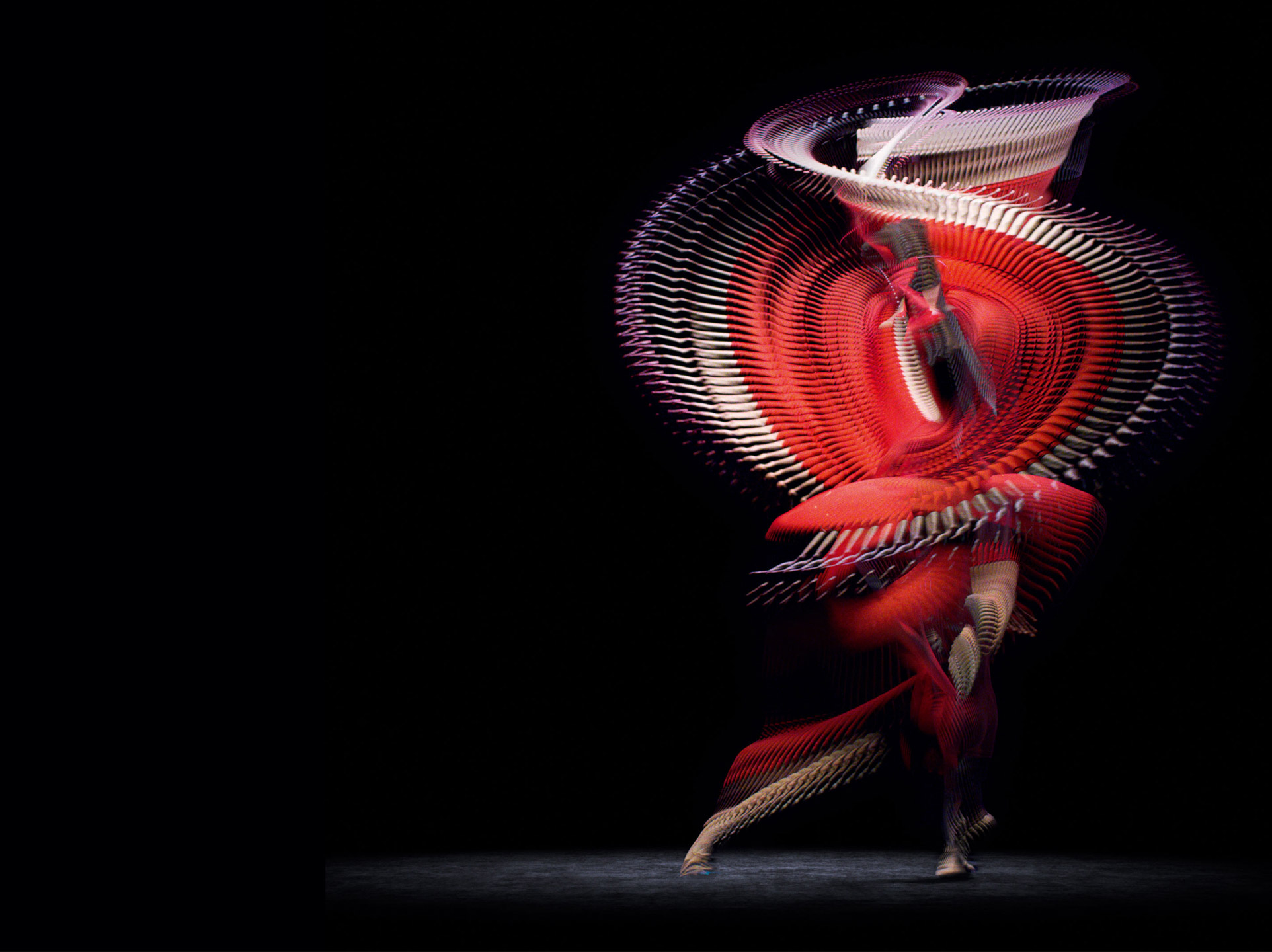 A dancer spins through a dark space, wearing a brilliant red dress which leaves traces through the air as she moves.