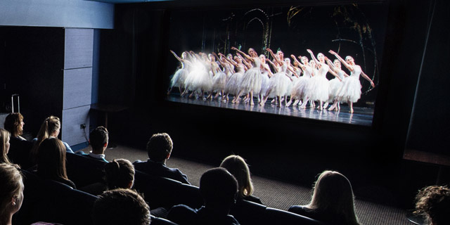 A crowd enjoys The Royal Ballet's production of Swan Lake at the cinema